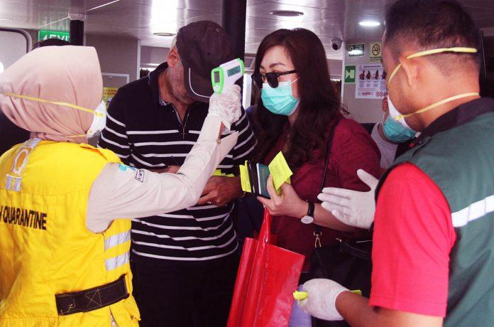 Petugas otoritas kesehatan memeriksa suhu tubuh seorang penumpang kapal dari Malaysia menggunakan termometer non kontak di Pelabuhan Internasional PT Pelindo I Dumai di Dumai, Riau, Minggu (23/2/2020).